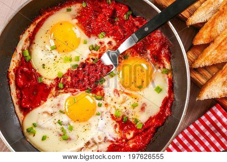 Frying pan with eggs in purgatory on table, close up