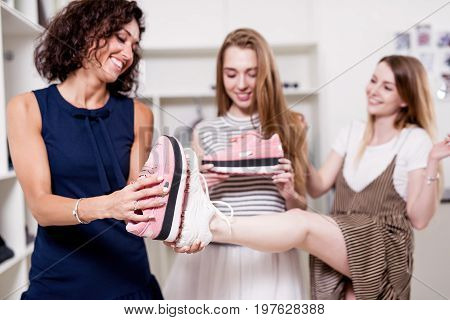 Young pretty lady standing at one leg while her friend checking new footwear size comparing it with old shoes sole. Positive girlfriends choosing sports boots in trendy boutique.
