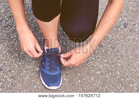Girl Ties Up Shoelaces In Sneakers On Road While Jogging, Legs And Sneakers, Toned Image