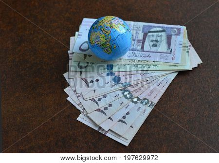 Saudi Rials currency notes along with miniature globe sphere showing Saudi map- Stock image. Spread of Saudi Riyal currency notes.