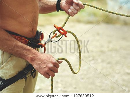 man belaying other climber through a belay device. Tubular device on locking carabiner. hands and belay device close up