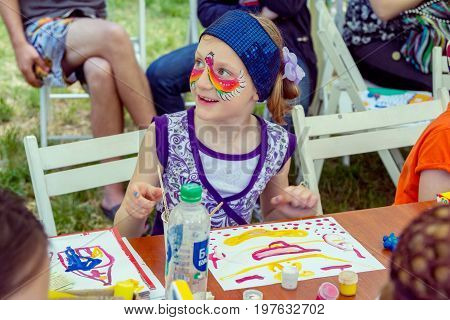 Zaporizhia/Ukraine- May 28, 2017: Charity Family festival: smiling  girl with painted face mask, participating at art and craft outdoors workshop, making colorful drawings with gouache