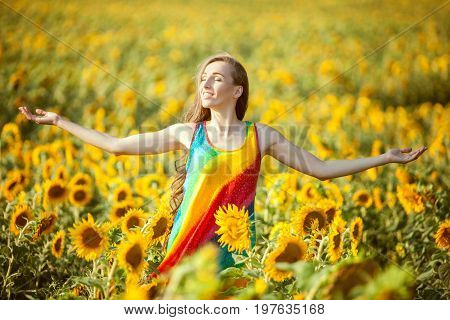 Woman smiles happily in the field standing among the blooming sunflowers.