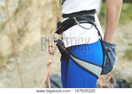 woman climber is preparing to climb on the rock. climbing harness with rope and chalk bag close up