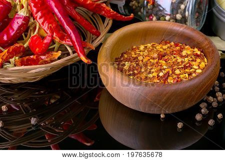 Red chili peppers and chili flakes on black background with reflection and copy space
