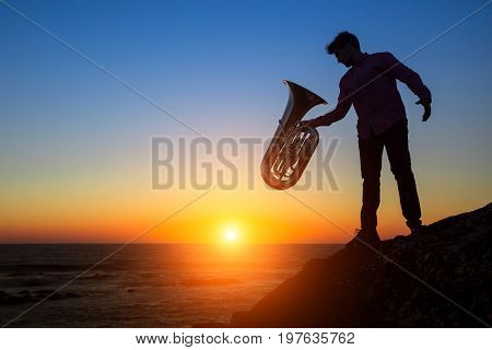 Silhouette of musician with the trumpet on rocky sea coast during amazing sunset. Tuba instrument.