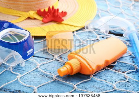 Sunscreen With Diving Mask, Snorkel And Hat On Wooden Table