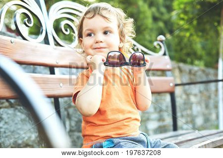 A little boy seats on the banch at summer evening in city park and play with sunglasses.