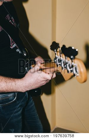 Guitarist with bass guitar in selective focus. Unrecognizable man with instrument closeup, hobby for adults. Music recording process