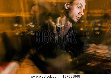 Guitarist creative portrait in double exposure. Music recording studio, split personality, dark psychological condition
