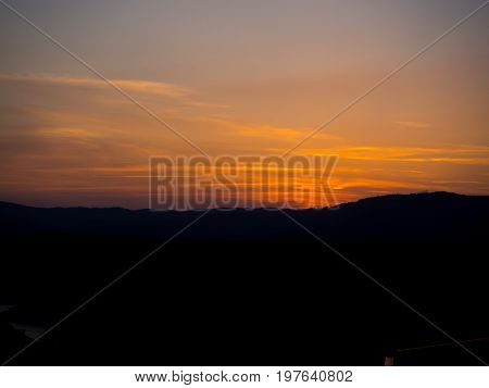 Sunset on the Spanish coast with silhouetted earth and predominance of orange color
