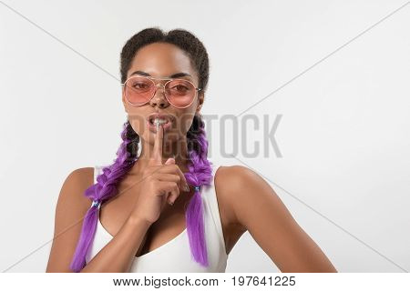 Stop talking. Portrait sexual african girl with purple synthetic braids is holding finger near her mouth while showing to be quiet. Isolated background with copy space in the right side