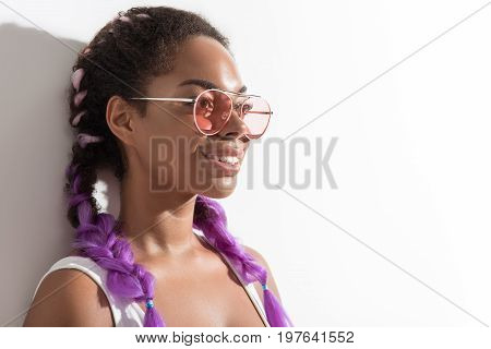 Trendy style. Positive glamorous mulatto girl is leaning on wall while standing with modern kanekalon braiding hair and looking aside with smile. Copy space in the right side