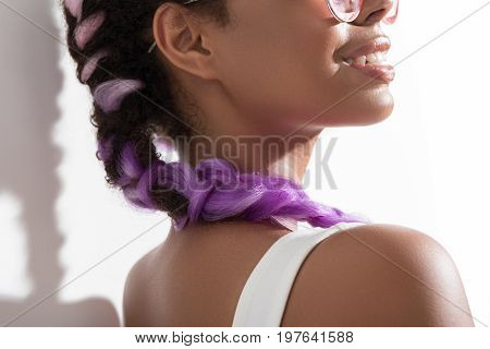 Synthetic hair extensions. Close-up of trendy violet braids of stylish african teenage girl using kanekalon hair which is standing with smile