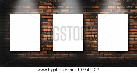 Three blank, white canvas frames hang on brick wall with Light shining down on them.Three blank billboards attached to a buildings exterior brick wall.