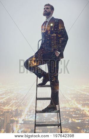 Standing on the top of career ladder. Successful businessman is looking up with confidence while city lights night view projection beneath him. Double exposure
