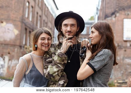Attractive young European man wearing trendy hat and camouflage jacket relaxing in urban setting with his two girlfriends enjoying good company. Three cheerful teenage friends having fun outdoor