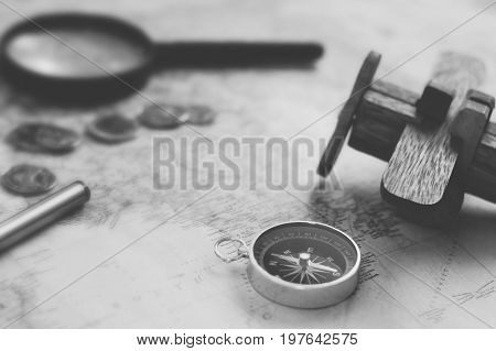 Compass ,coins and Wooden plane on world map, selective focus ,black and withe vintage  style.