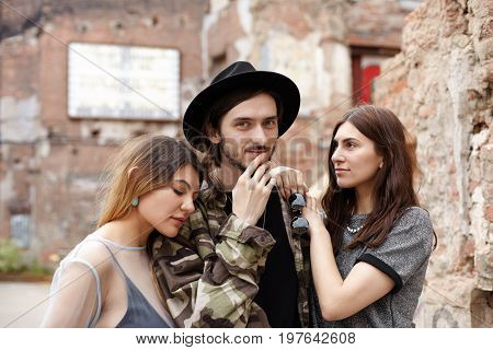 Outdoor portrait of happy fashionable young Caucasian male in hat standing outdoors between two cute young women who are in love with him. Love dilemma relationships romance and dating concept