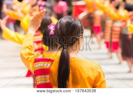 Thai festival dancers with pink flower hairpin in local yellow dress dancing