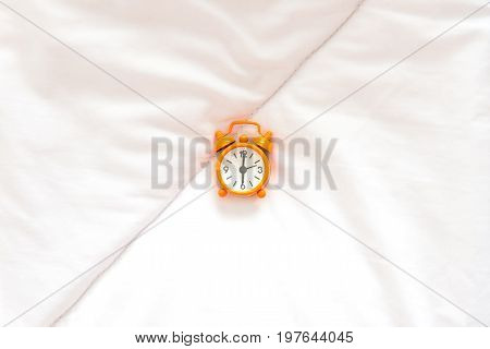 Orange Alarm clock get up six o'clock on bed in morning with sun light. Lifestyle Concept