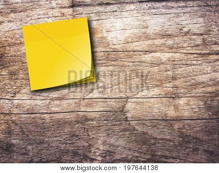 Yellow reminder sticky note on wooden wall background,empty space for text.