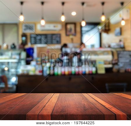 Empty brown wooden table surface and coffee shop interior blur background with bokeh image, for product display montage,can be used for montage or display your products.