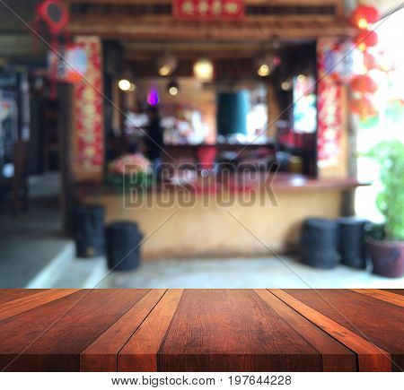 Empty brown wooden table surface and cashier counter blur background with bokeh image, for product display montage,can be used for montage or display your products.