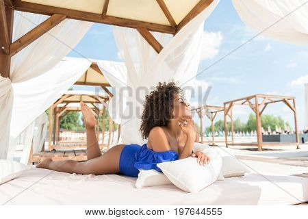 Cheerful young agrican woman is lying on large wooden sun bed with roof and drapes. She is leaning her elbows on soft pillows and looking with enjoyment on beach