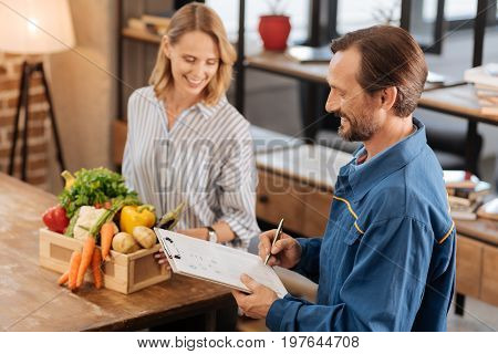 One more to go. Attentive intelligent nice guy crossing another task from his list while fetching some vegetables to lady ordering them