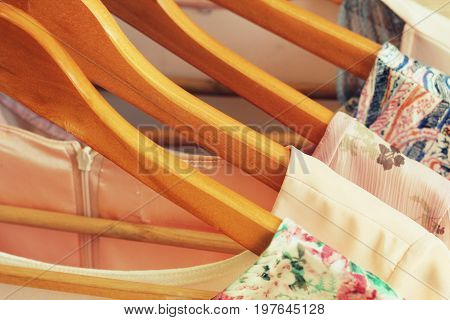 collection of women's clothes hanging on rack .