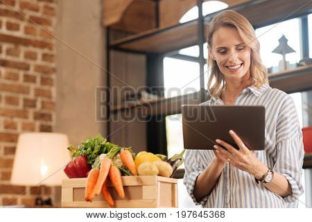 Online search. Motivated savvy active lady using her gadget for making purchase and looking for cooking instructions while taking care of her diet