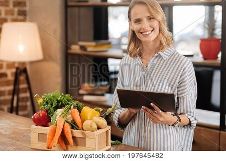 Looking for instructions. Young graceful pretty woman standing at the table and looking for the right recipe while having all the ingredients on front of her