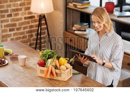 What should i cook. Excited savvy committed lady using her tablet for searching for the right recipe while having many vegetables on her table