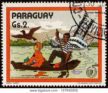 Moscow Russia - July 30 2017: A stamp printed in Paraguay shows Finn and Joe in boat near Sinking Riverboat Adventures of Tom Sawyer by Mark Twain series