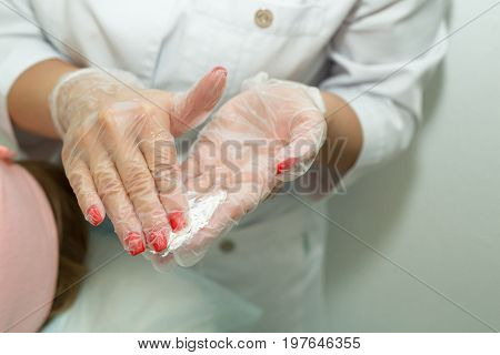 Hands of the beautician in gloves, diluted cream face mask in the salon