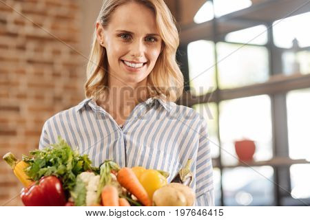 Freshness from the inside. Attractive optimistic charming lady holding a box filled with vegetables while taking care of her healthy and being a vegetarian