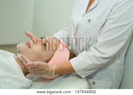 Beautiful young girl on facial cleansing procedure at a cosmetologist