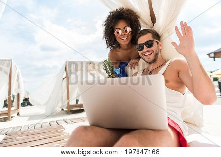 Portrait of cheerful youthful bearded man and mulatto woman communicating via laptop with friends. They are smiling through sunglasses and sending hello