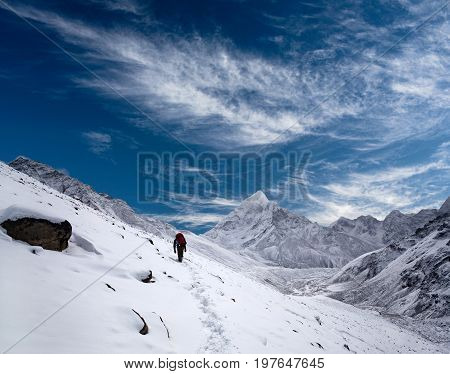 An unidentified tourist walking on the road to Everest Base Camp in Sagarmatha National Park Nepal Himalaya
