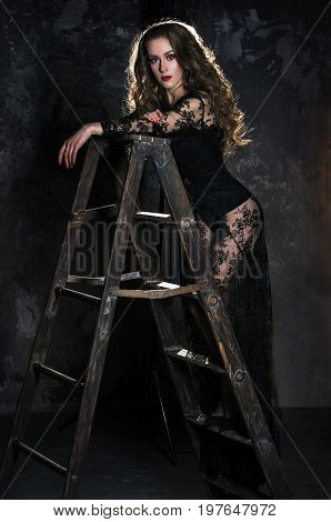 An attractive young woman in a long black dress is standing on a ladder, a ladder against a grunge wall.