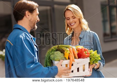 Fresh ingredients. Enchanting attentive incredible leady meeting the delivery guy who fetching her vegetables she ordering from nice store nearby poster