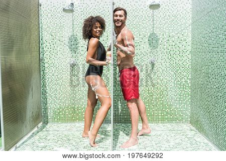 Full length portrait of happy youthful bearded man and mulatto woman touching separation wall of shower cubicles. They are covered with soap foam and laughing