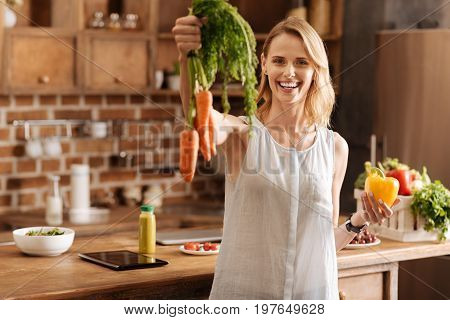 Positive vibes. Elegant energetic nice woman using fresh veggies for making food at home while taking care of her health and body at once