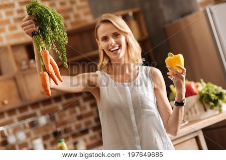 Energetic lady. Wonderful energetic passionate woman standing in the kitchen and choosing ingredients for her meal while following vegetarian diet