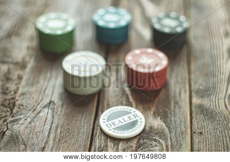 Close-up poker color chips with dealer chip on dark old wood table. Selective focus