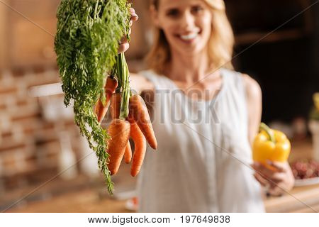 Sweet and bright. Charismatic vibrant clever woman enjoying fresh vegetables while making a meal at home and sticking to vegetarian diet