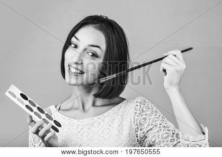 girl with short hair in tracery blouse with paint and long paintbrush smiling black and white