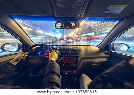 Two man in a car moves at fast speed at the winter night. Blured road with lights with car on high speed.