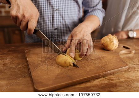 Domestic chef. Curious vibrant cheerful guy spending time in the kitchen and cooking a dinner at home while using fresh vegetables